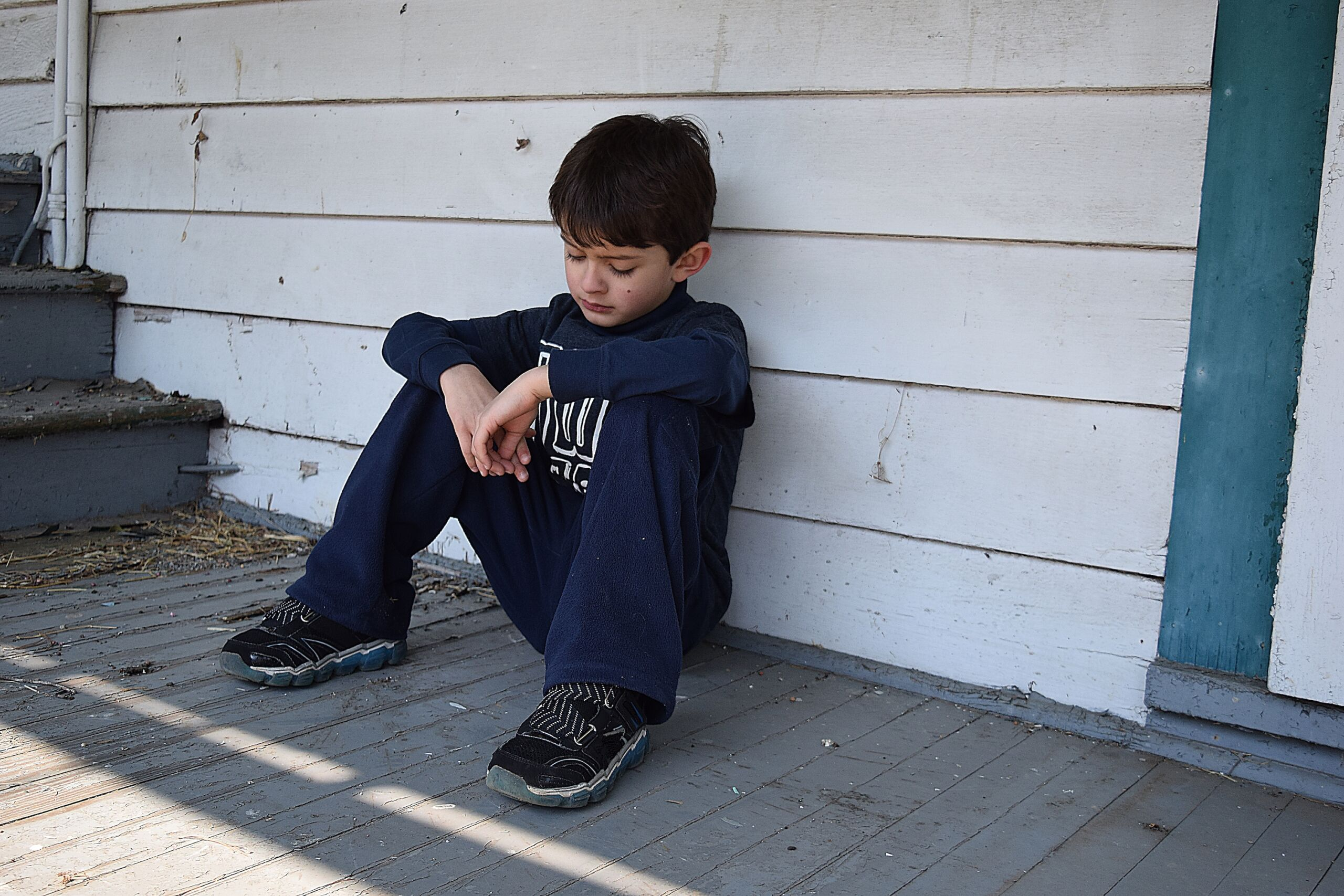 Male child around 6-10 years of age sitting down out on a porch. His head is down looking upset