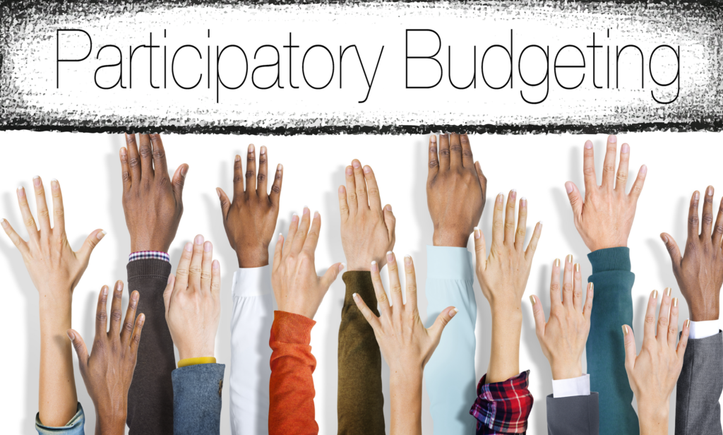 """Hands reach toward the phrase """"participatory budgeting"""""""
